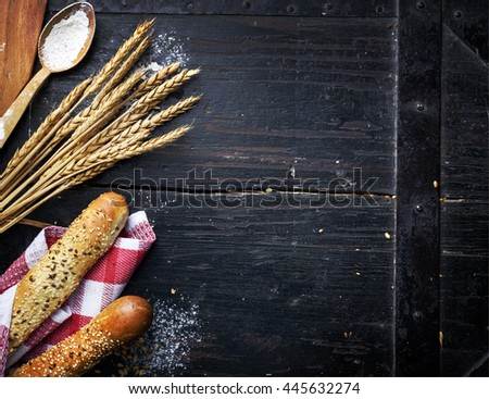 Bread, wheat ears and flour on rustic black table.