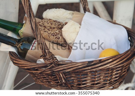 Bread, wine and lemon in a wicker basket. Food and beverages - stock photo