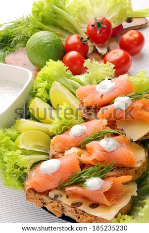 Bread with cheese, salmon and dill dip on wood background