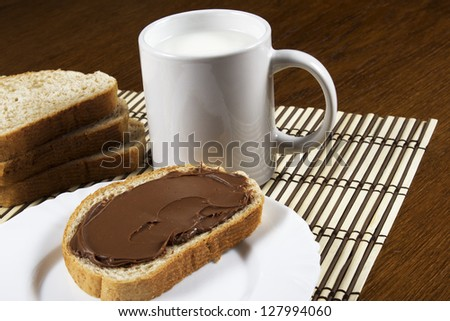 bread with chocolate and a glass of milk - stock photo