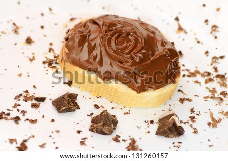 Bread with chocolate cream and chocolate pieces on a plate