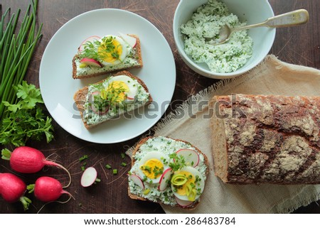 Bread with cottage cheese with herbs and boiled egg - stock photo