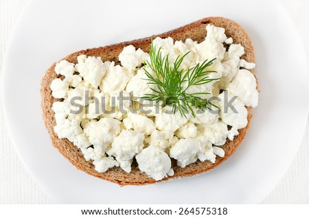 Bread with curd cheese and dill on white plate, top view, close up - stock photo