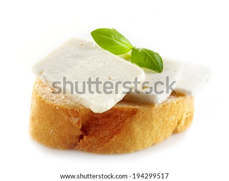 bread with fresh goat cheese and basil on a white background