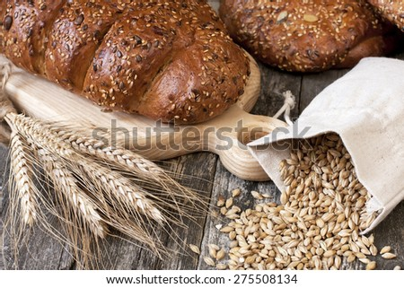 Bread with grain on wooden background - stock photo