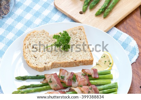 bread with green asparagus and butter on a white plate.  - stock photo