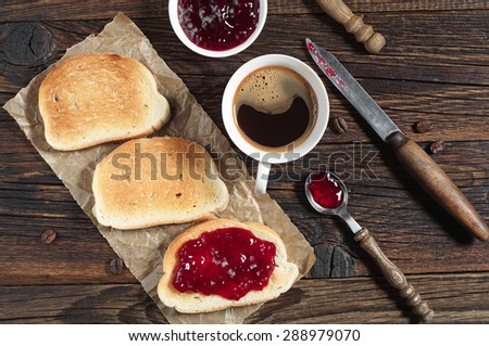 Bread with jam and coffee cup for breakfast on rustic wooden table, top view - stock photo
