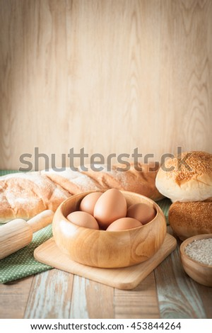 Bread with kitchen utensils on vintage wooden background