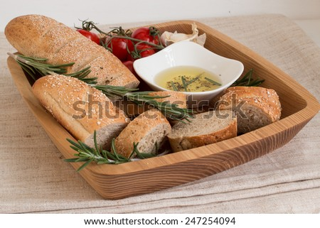 Bread with olive oil ,rosemary,tomato and garlic on the wooden plate.