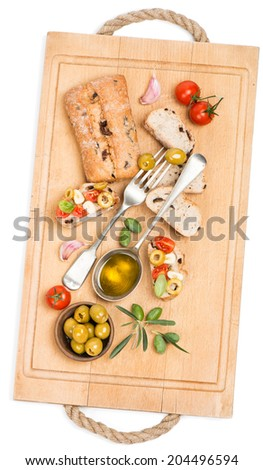 Bread with olives, tomatoes, garlic and olive oil  on a wooden kitchen board, top view. Isolated on white. - stock photo