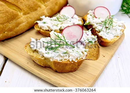 Bread with pate of cottage cheese, dill and radish on a wooden board, a napkin on a background of a wooden table - stock photo