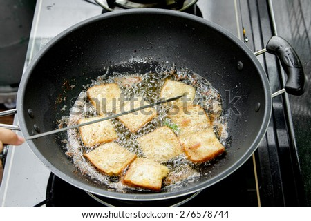 bread with raw minced pork spread frying in pan