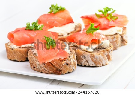 Bread with smoked salmon and cream cheese on white plate, close up view - stock photo