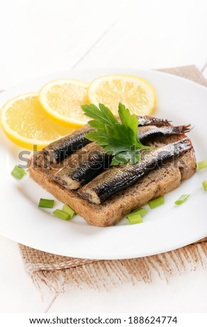 Bread with sprats on a white plate - stock photo