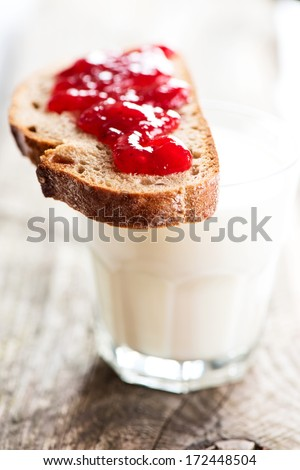 Bread with strawberry jam and glass of milk on wooden table - stock photo