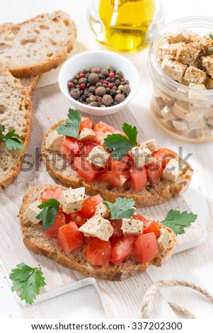 bread with tomatoes and marinated feta, top view, vertical - stock photo