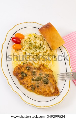 Breaded chicken baked to a golden brown in lemon garlic butter sauce and topped with capers.  Served with pasta garnished with parsley.  Vertical from overhead on white background with copy space. - stock photo