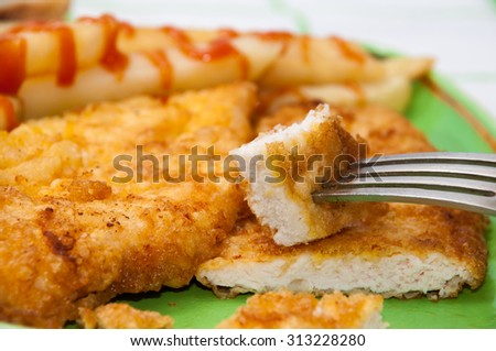 Breaded chicken breast on a fork stuck in focus with a plate in the background. - stock photo