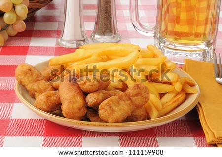 Breaded chicken strips with french fries and beer - stock photo