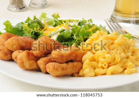 Breaded chicken strips with macaroni and cheese and salad
