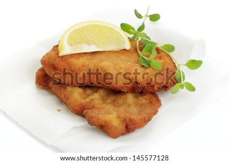 Breaded cutlet with lemon wedges - stock photo