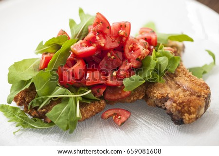 Breaded cutlet with rucola and raw tometoes