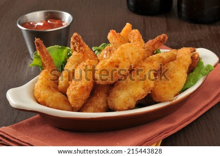 Breaded deep fried butterfly shrimp with cocktail sauce and beer - stock photo