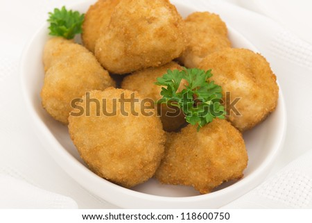 Breaded deep fried mushrooms garnished with parsley. Party food table set up shot from above. - stock photo