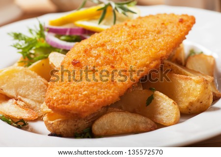 Breaded fish steak with baked potato served on a plate