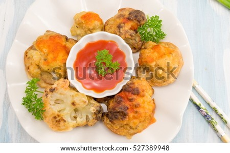 breaded fried cauliflower with chopsticks and ketchup on a plate
