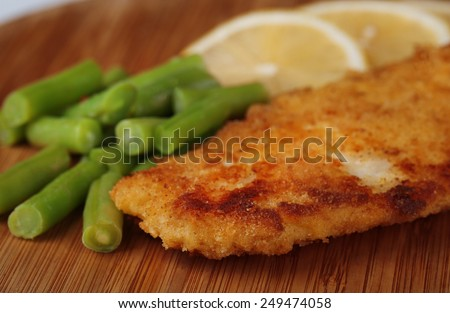 Breaded fried fillet and potatoes with asparagus and sliced lemon on wooden cutting board background - stock photo