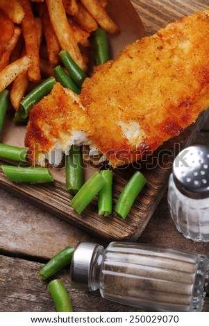 Breaded fried fish fillet and potatoes in paper bag with asparagus on cutting board and rustic wooden background - stock photo