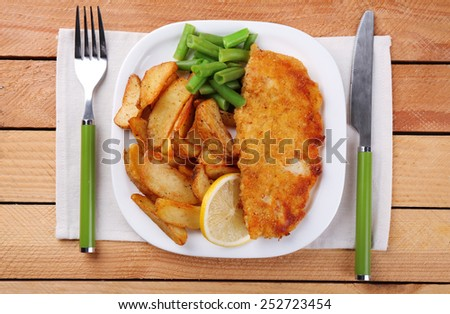 Breaded fried fish fillet and potatoes with asparagus and lemon on plate with napkin and cutlery on wooden planks background - stock photo