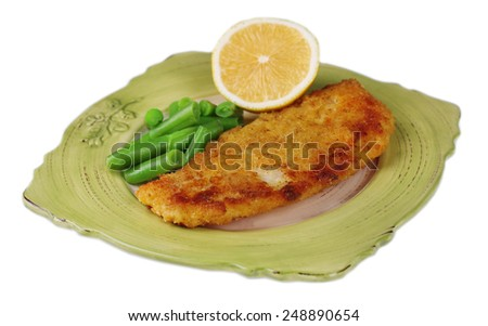 Breaded fried fish fillet and potatoes with asparagus and sliced lemon isolated on white - stock photo
