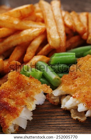 Breaded fried fish fillet and potatoes with asparagus on wooden cutting board background - stock photo