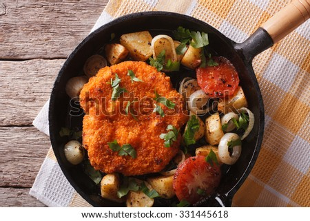 breaded German Weiner schnitzel with fried vegetables in a pan close-up on the table. horizontal top view - stock photo