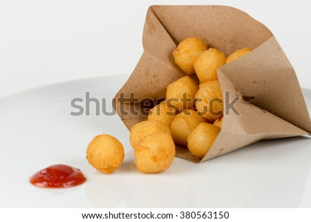 Breaded potato croquettes in a paper bag with ketchup isolated on white - stock photo