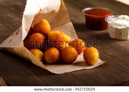 Breaded potato croquettes with red and white sauce on a wooden table close-up. horizontal - stock photo