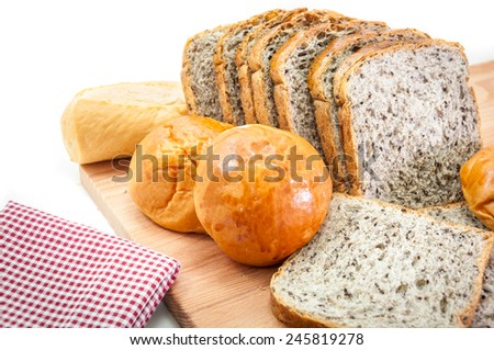 Breads on piece of wood with fabric on white background, selective focus at middle of image