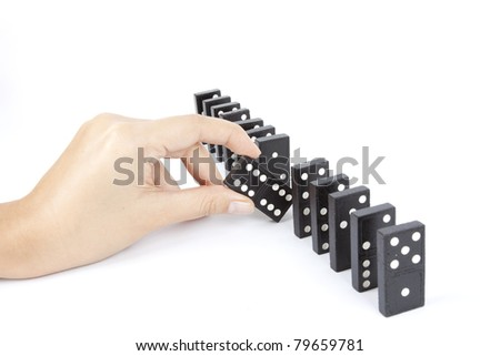 break, a hand breaking dominos line. - stock photo
