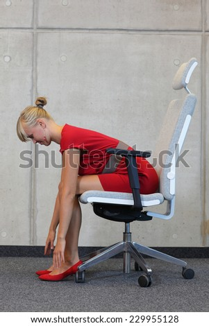 break at work in office - relax on chair  - business woman exercising - stock photo