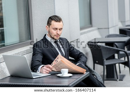 Break for lunch. Handsome businessman with beard reading a newspaper at the table and working on laptop.