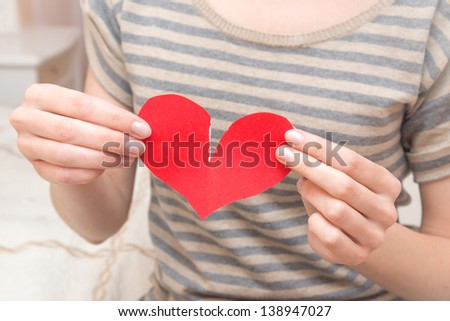 Break red heart in beautiful female hands (fingers) in bedroom. Conflict in couple, problems, divorce and pain concept.