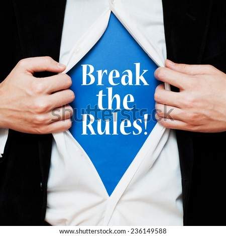 Break the Rules! Businessman showing a superhero suit underneath his shirt with a motivational message text written on it. - stock photo