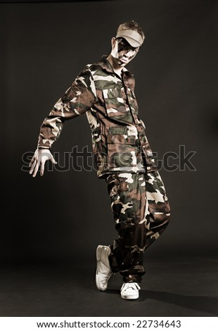 breakdancer in camouflage dancing against dark background