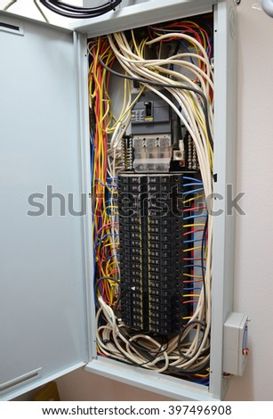 Breaker box with circuit-breakers and tangled cable leads - stock photo