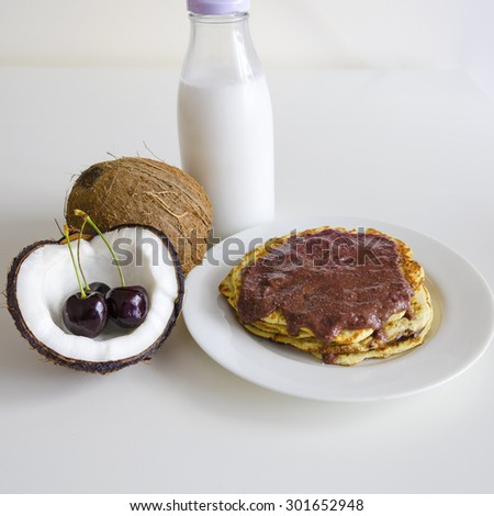 Breakfast and brunch coconut pancakes meal with cracked open coco, glass bottle of milk and cherry on white background. Stack of crepes is topped with cream syrup ready to eat. - stock photo