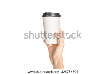 Breakfast and coffee theme: man's hand holding white empty paper coffee cup with a brown plastic cap isolated on a white background in the studio, advertising of coffee first-person view - stock photo