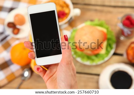breakfast and mobile on wooden tablet - stock photo