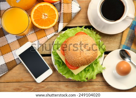 breakfast and moile phone on wooden table - stock photo